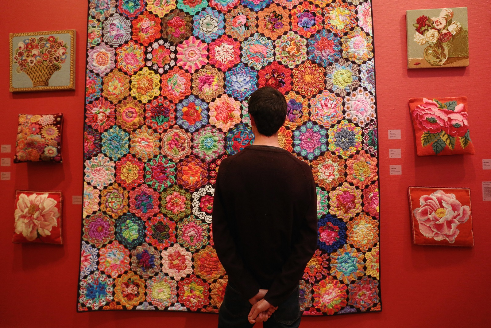 Image: A visitor viewing a quilt