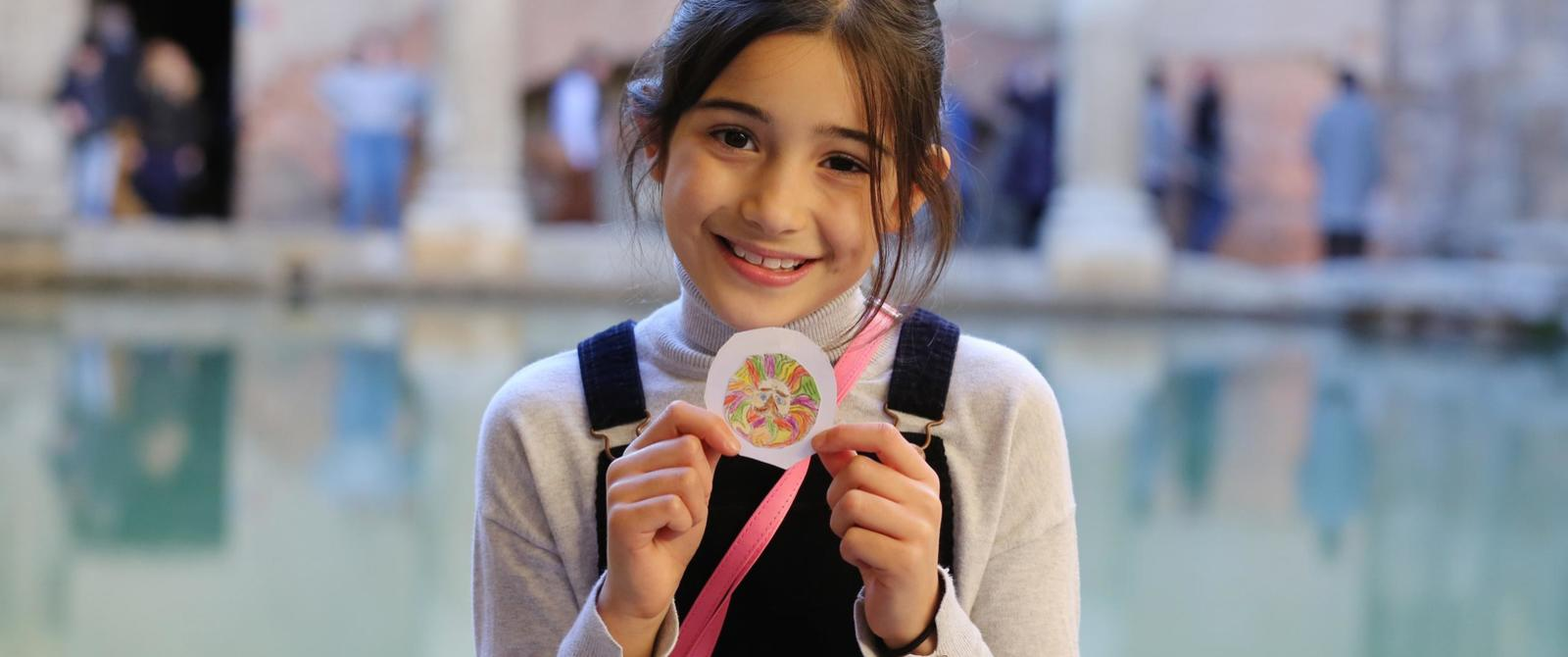 Image: A child showing her finished fridge magnet