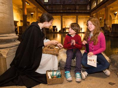 Image: Looking at artefacts beside the Great Bath