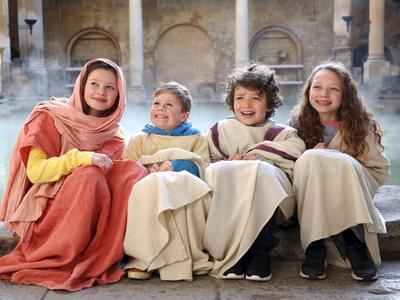 Image: Children dressed up in togas beside the Great Bath